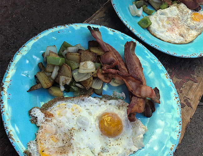 Campfire cooking breakfast fried eggs, bacon, and potatoes | RIZNWILD